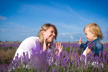 Little girl playing with her mother in lavender field