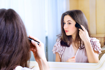 Portrait of  beautiful young woman looking at the mirror