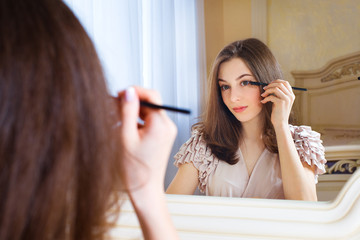 Portrait of  beautiful young woman putting mascara