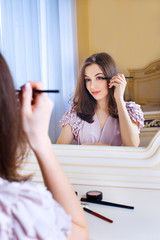 Portrait of  beautiful young woman putting on makeup holding a b
