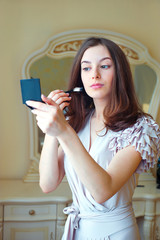 Portrait of  beautiful young woman putting on makeup