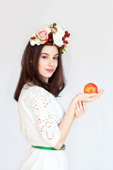 Portrait of beautiful girl with flower wreath holding apple