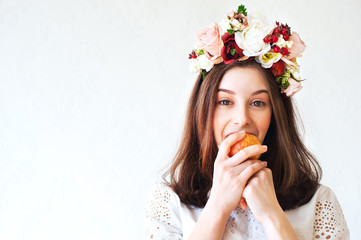 Portrait of beautiful girl with flower wreath eating apple