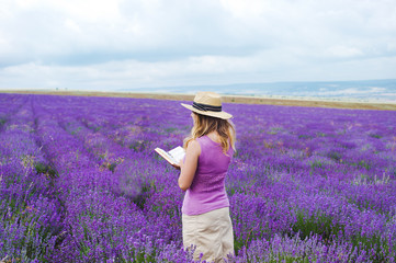 Woman in lavender field with book