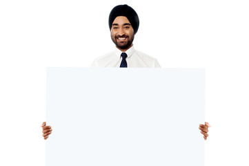 Smiling young man holding white sign board