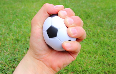 Small stress ball in hand of man on grass background