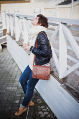 Fashion young woman drinking coffee on the street