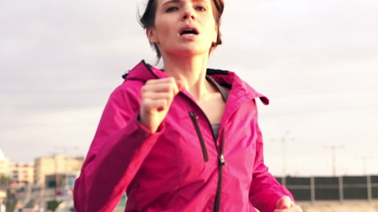 Young woman jogging in the city, super slow motion