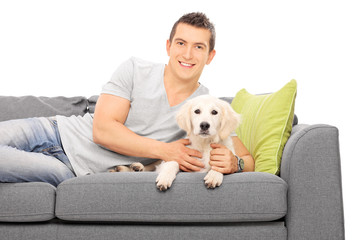 Young man lying on couch with a puppy