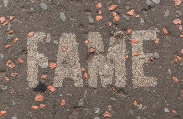 """""""Fame"""" written in white capital letters on a street pavement"""