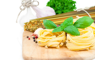 Italian pasta fettuccine nest with fresh basil leaves, on white