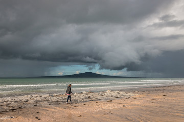 woman walking on Takapuna beach at storm