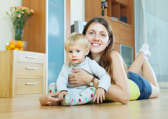 woman with toddler on on wooden floor in home
