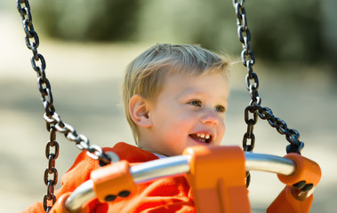 laughing toddler on orange swing