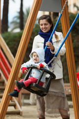 woman with  toddler on swings