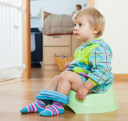 Baby girl sitting on green potty