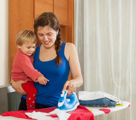 Housewife with baby ironing  at home