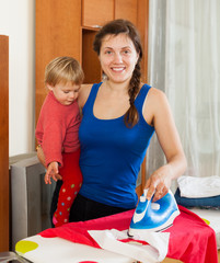 Girl with baby ironing