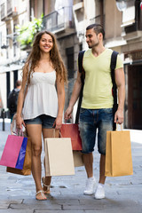 happy young loving pair with shopping bags at city
