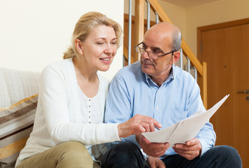 Mature couple with documents at home