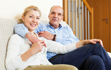 happy mature couple together in home interior