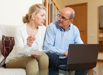 Woman reading finance documents with husband