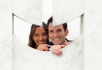 Fun couple peeping through a hole in a sculpture