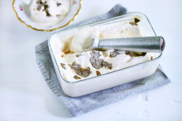 Ice cream scoop in ice box with caramel ice cream and truffles