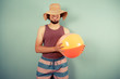 Happy young man with beach ball and sun hat