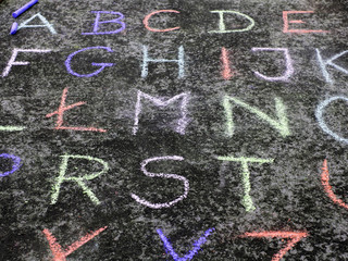 alphabet written in colorful chalk on the asphalt