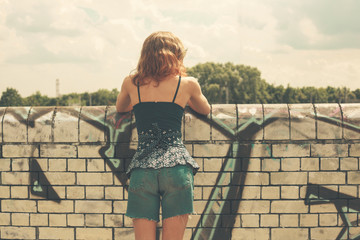 Young woman looking over wall