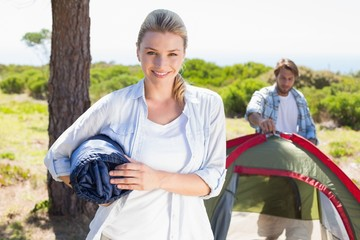 Attractive blonde smiling at camera while partner pitches tent