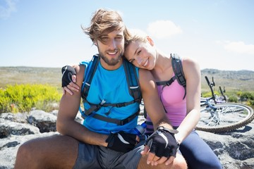 Fit cyclist couple taking a break on rocky peak smiling at camer