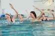 Female fitness class doing aqua aerobics - 67529553