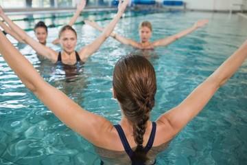 Smiling female fitness class doing aqua aerobics