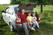 Three cheerful child sitting in the trunk of a car on nature