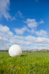 Football on pitch under blue sky