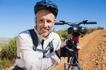 Fit cyclist carrying his bike on country terrain