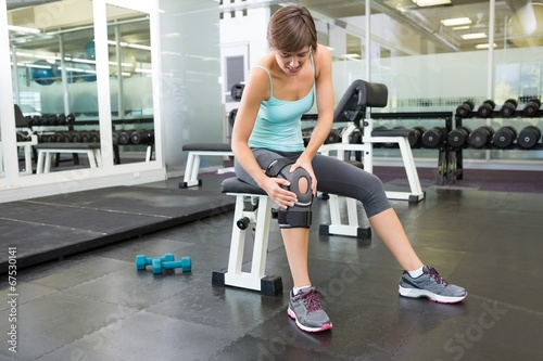 Foto op Aluminium Gymnastiek Fit brunette sitting on bench holding injured knee