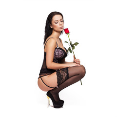 Sexy woman in corset and stockings squat with rose
