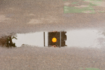 Amber traffic light reflection in puddle
