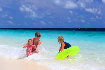 mother with kids swimming on sea vacation