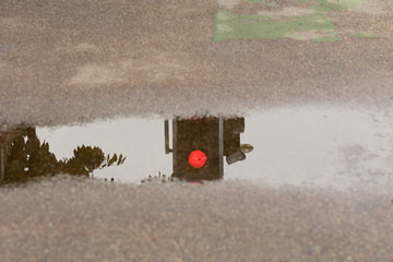red traffic light reflection in puddle