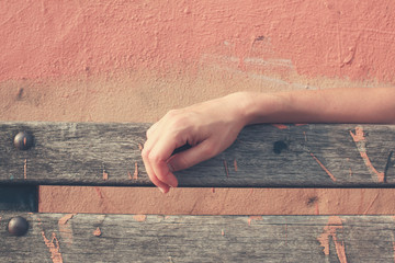 Female hand resting on bench