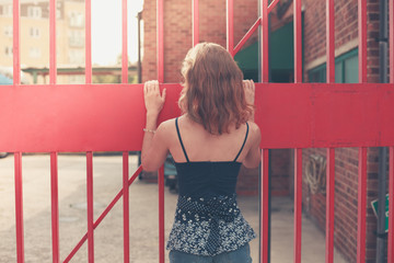 Young woman standing by a gate outside