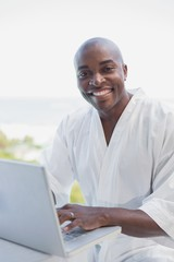 Handsome man in bathrobe using laptop outside