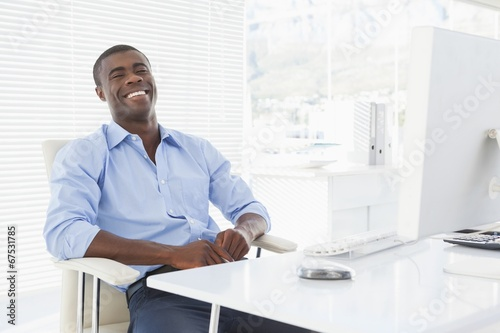 Happy businessman sitting at his desk
