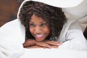 Attractive woman smiling under the duvet