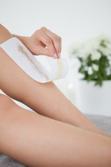 Woman waxing her legs herself