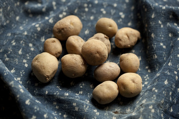 Raw potatoes on blue fabric